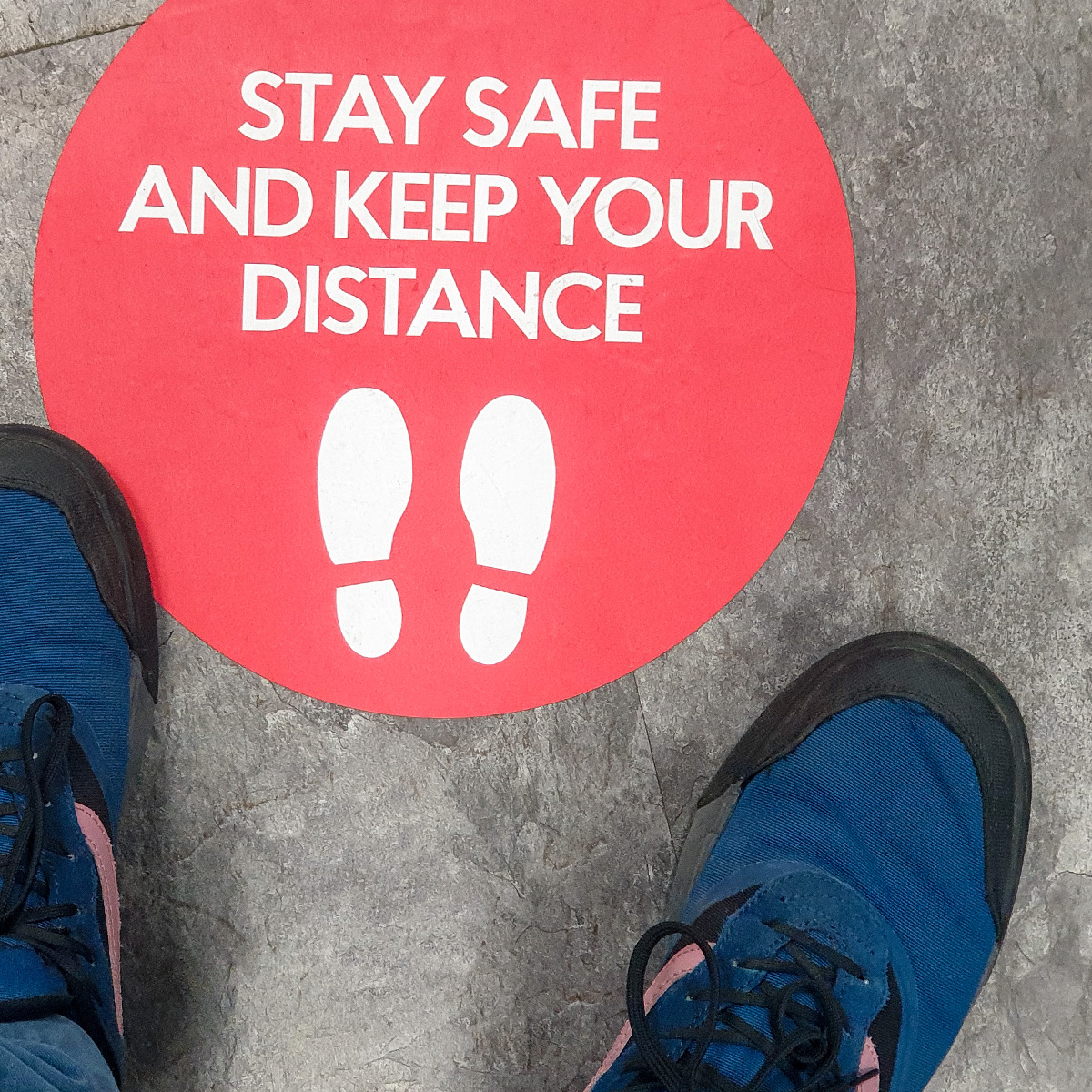 Stay safe and keep your distance graphic on floor